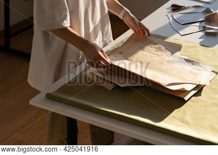 Fashion Designer Hold New Sewing Patterns On Craft Paper, Unrecognizable Closeup. Female Tailor Work