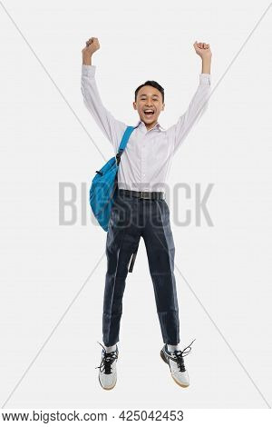 A Boy Jump Wearing Junior High School Uniform Smiling With Raised Hands Carrying A Backpack