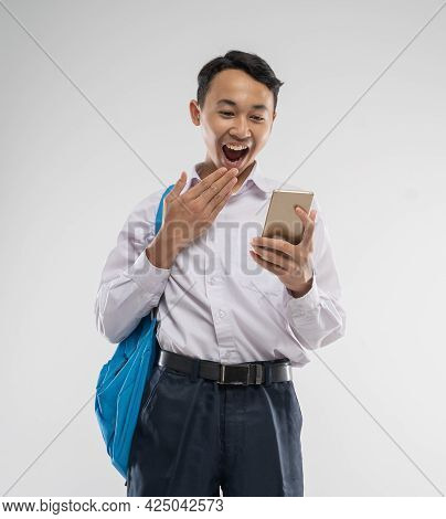 A Asian Boy Wearing A Junior High School Uniform Holding A Cellphone With A Surprised Expression And