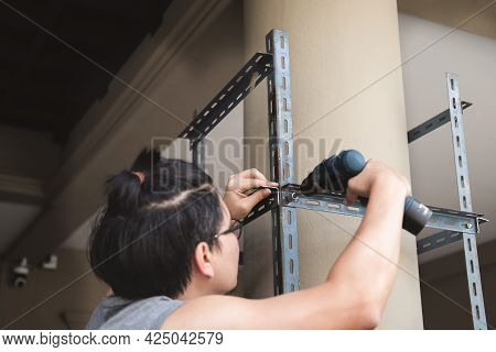 Do It Yourself Concept, Craftsmen Use Electric Drills To Assemble Old Iron Parts. Make A Shelf On Yo