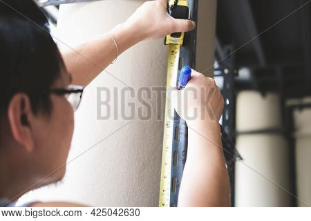 Do-it-yourself Concept Craftsmen Use Height Measuring Tapes To Assemble Old Iron Parts. Make A Shelf