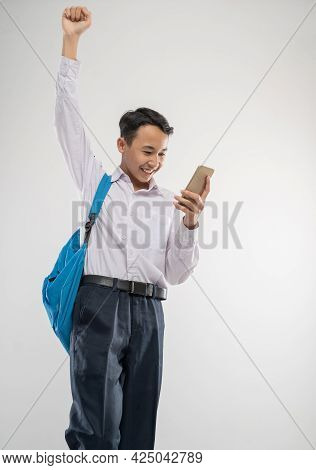 A Excited Boy Wears A School Uniform Using A Handphone While Raises His Hand And Carries A Backpack