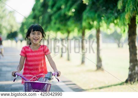 Little Girl Enjoy Ride Bike In The Park