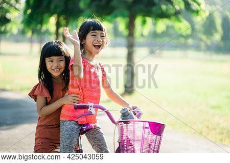 Two Kids Enjoy Ride Bike In The Park Togethe