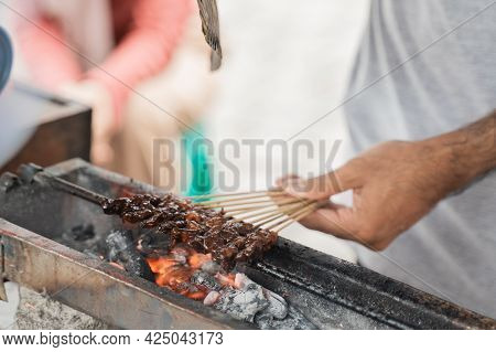 Hand With Traditional Chicken Satay Skewer In Charcoal Grill