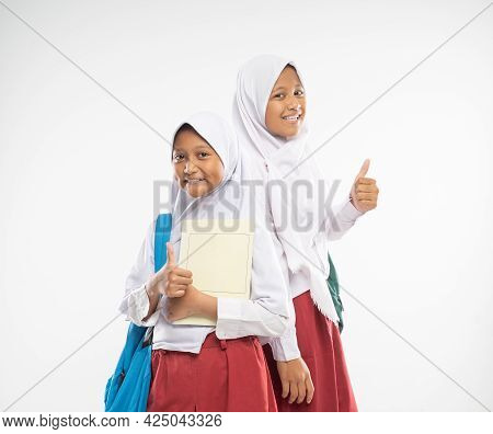 Smiling Two Veiled Girls Wearing Elementary School Uniforms With Thumbs Up Carrying Backpacks And A