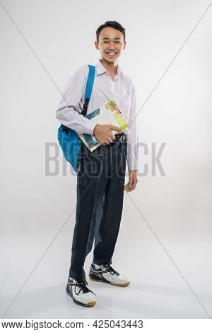 A Boy Standing In Junior High School Uniform Smiling Holding A Book And School Bag