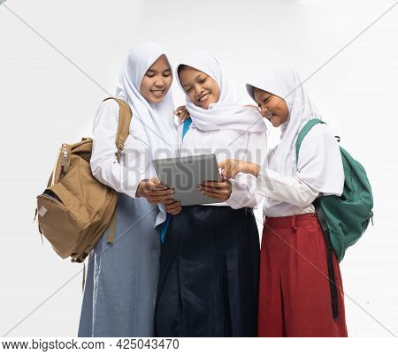 Three Veiled Girls Wearing School Uniforms Using A Digital Tablet Together While Carrying A Backpack