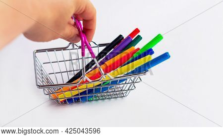 A Miniature Shopping Basket With Colored Markers, Close-up In A Woman's Hand. The Hand Holds Colored