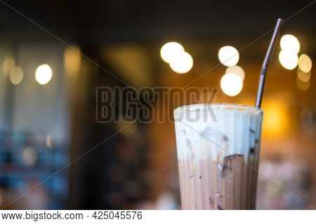 A Glass Of Iced Mocha In Cafe With Orange Bokeh Background