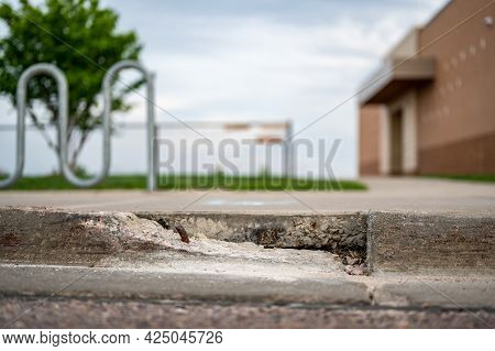 Broken Sidewalk Curb With Exposed Rebar And Jagged Edges That Could Cause A Tripping Hazard