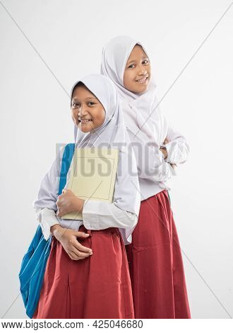 Two Asian Veiled Girls Wearing Elementary School Uniforms Stand Back To Each Other While Carrying A