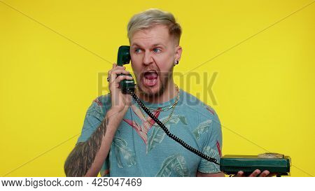 Crazy Sincere Tourist Adult Man 30s Years Old In Blue T-shirt Talking On Wired Vintage Telephone Of
