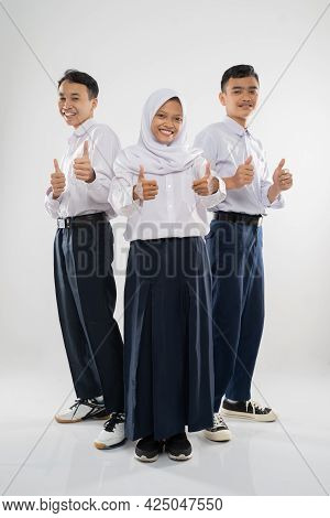 Three Teenagers Wearing Junior High School Uniforms Standing With Thumbs Up