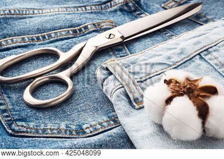 Blue Jeans, Scissors, Metal Reels With Thread Close-up. Tailoring Of Casual Denim Clothing Concept.