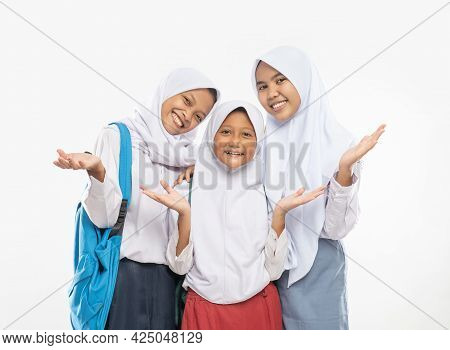 Three Girls In Veils Wearing School Uniforms Stand With Hands Gesture Offering Something While Carry