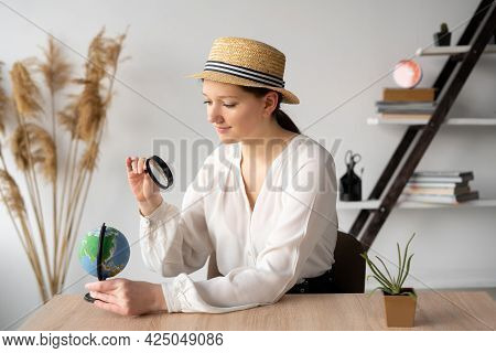 Girl Traveler At The Table In The Office Looks At The Globe Through A Magnifying Glass. A Teenager A