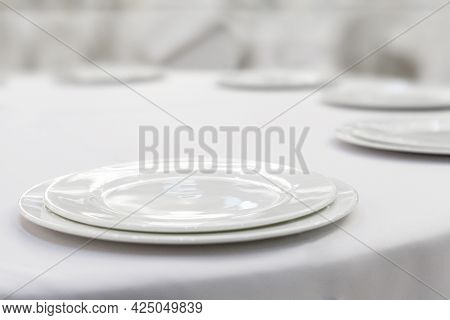 Empty White Plates On A White Tablecloth. Restaurant Setting.