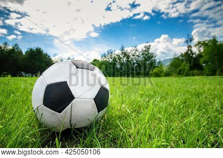 Football Soccer Ball On Green Grass Field On Summer Sky Background With Copy Space.