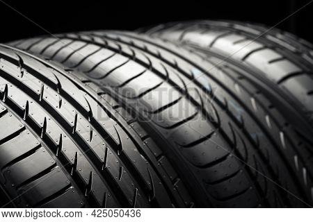 Three New Car Tires On A Dark Black Background