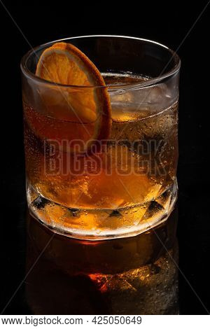 Alcoholic cocktail Old fashioned cocktail with orange slice and lump sugar on black background. Copyspace