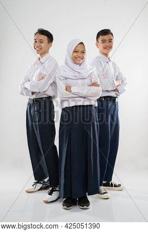 Three Teenagers Wearing Junior High School Uniforms Standing With Crossed Hands