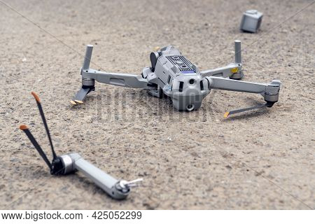 The Fall Of The Drone. A Broken Flying Quadcopter Is Lying On The Asphalt, The Propeller Has Flown O
