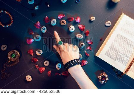 Concept Of Astrology And Horoscope. A Woman's Hand Points To The Stones With The Signs Of The Zodiac
