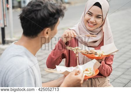 Couple Enjoy Eating Chicken Satay They Bought From Street Food Seller In Indonesia