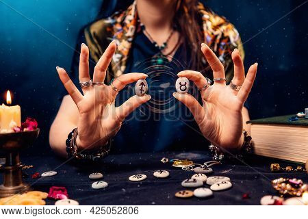 Astrology And Horoscope. A Woman Holds Stones With The Zodiac Sign Of Taurus And Sagittarius. The Co
