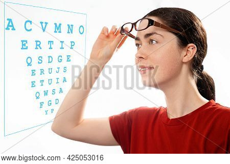 Ophthalmology. Portrait Of A Young Beautiful Woman Taking Off Her Glasses And Looking At A Diagram T
