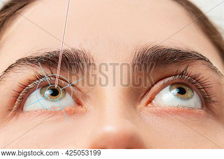 Close Up Of Woman's Eyes Looking Up And Laser Beam Lighting At Pupil Of The Eye. The Concept Of Lase