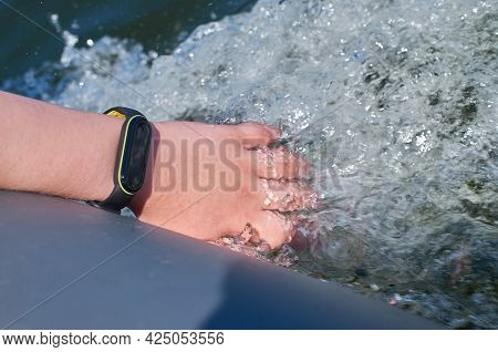 A Teenager's Hand With A Waterproof Fitness Bracelet Is Lowered Into The Water.