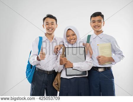 Three Teenagers In Junior High School Uniforms Holding A Laptop Computer With Thumbs Up When Carryin