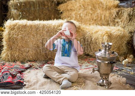A Child Boy In An Embroidered Shirt Sits On A Burlap With A Samovar And Drinks Tea Against The Backg