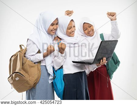 Three Asian In Veils Wearing School Uniforms Stand Using A Laptop Together With Excited Gestures And