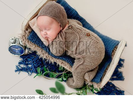 Sweet newborn baby boy sleeping in the little bed wearing knitted suit and hat. Beautiful infant child portrait
