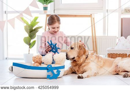 Little girl playing role marine games with golden retriever dog. Sea ship toy and child