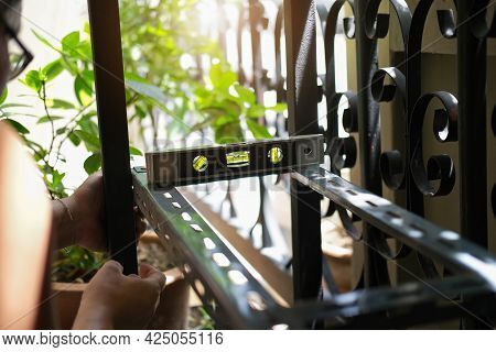 Do It Yourself Concept, Craftsman Uses A Water Level Gauge To Assemble Old Iron Parts. Make A Shelf