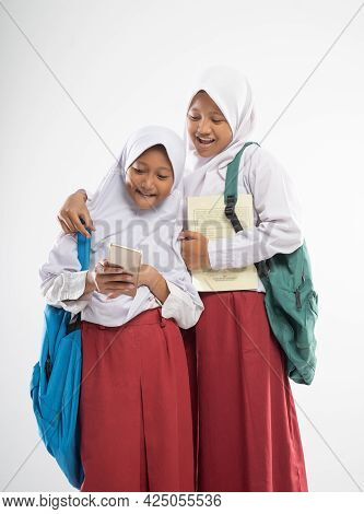 Two Asian Veiled Girls Wearing Elementary School Uniforms Using A Smartphone Together When Carrying