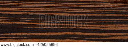 Natural Ebony Veneer Background In Elegant Brown Colors. Natural Wood Texture, Pattern Of A Long Ven