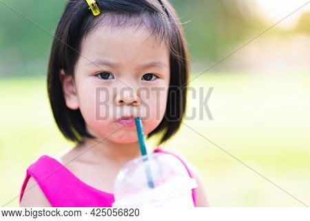 Head Shot Of Asian Baby Girl Drinking Coconut Smoothie. Cute Kid Sucking Sweet Water With Green Tube