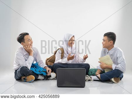 Three Teenagers In Junior High School Uniforms Sitting On The Floor Studying Together And Chatting W