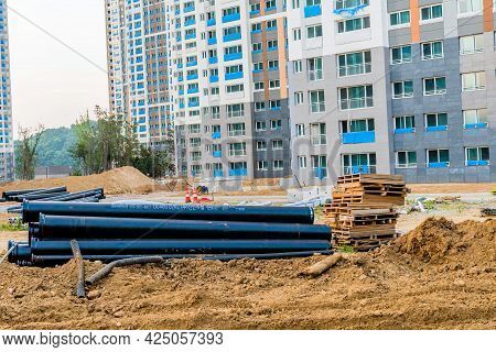 Daejeon; South Korea; June 20, 2021: Large Pvc Pipes Stacked Next To Wooden Pallets At Construction