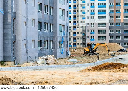 Daejeon; South Korea; June 20, 2021: Small Hyundai Backhoe Sitting Idle At Construction Site In Sint