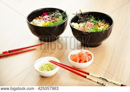 Two Poke Salads With Beef And Tuna In A Bowl On A Restaurant Table. Poke Salads In A Bowl Next To Ch