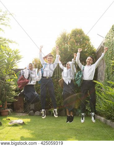 Four Teenagers Hopping Cheerfully In Junior High School Uniforms At The Graduation Announcement