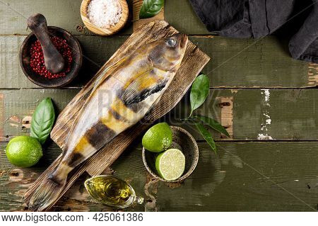 Raw Fish Sea Bass Or Lingcod And Seasonings For Cooking It On An Old Plank Background Top View, Free