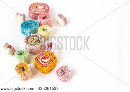 Different Shaped Colorful Jelly Candies Scattered On White Background