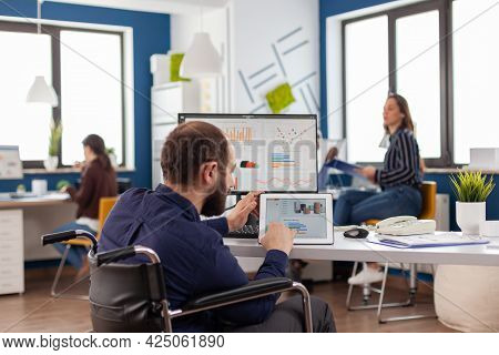 Handicapped Invalid Man Employee Sitting Immobilized In Wheelchair Working At Notepad And Computer I